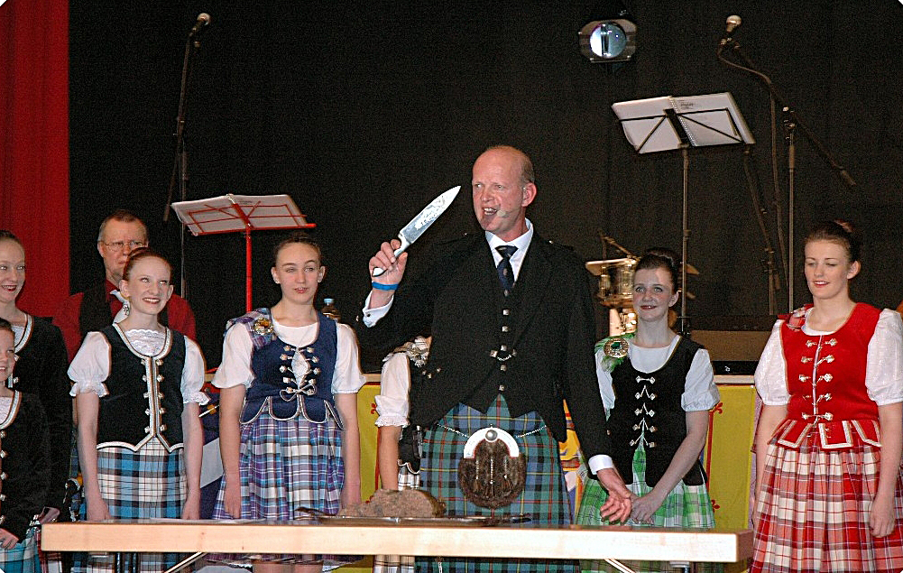 Man ready to cut the haggis, surrounded by dancers.
